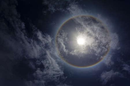 Sun with sircular rainbow, clouds and blue sky photo