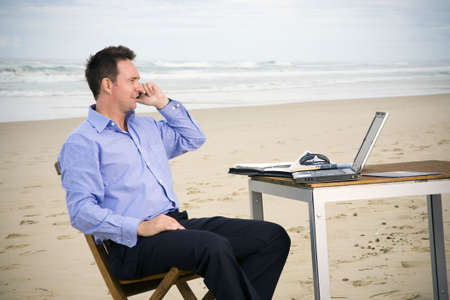 Business man with office on the beach photo