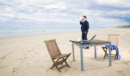 online trading: Business man with office on the beach Stock Photo