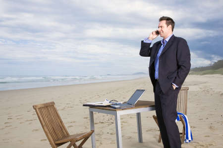 Business man with office on the beach Stock Photo