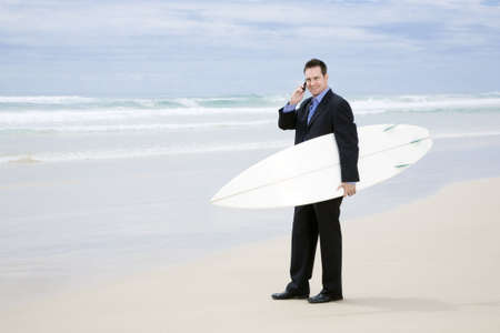Business man in suit walking with surfboard on the beach Stock Photo
