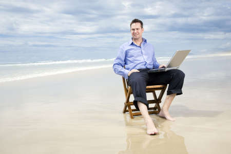 business man sitting on a chair on the beach with laptop