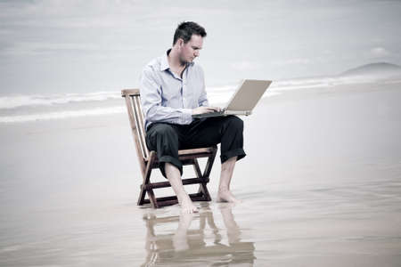 online trading: business man sitting on a chair on the beach with laptop