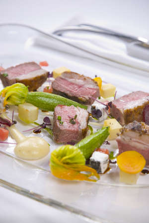 Lamb served with vegetables and sauce photo