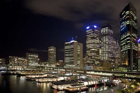 Sydney CBD at night from Circular Keys with ferries and terminal in foreground