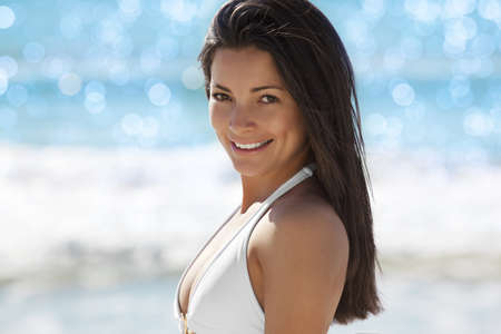 Beautiful young woman smiling at the beach photo