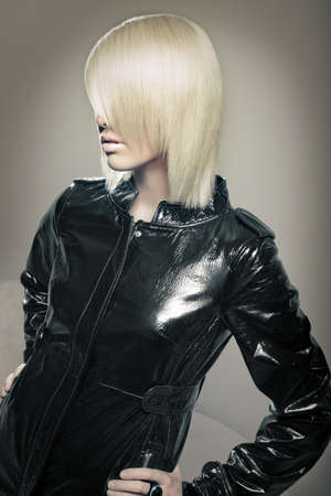 Beautiful young blond fashion model with leather jacket. beauty shot of Hair. photo