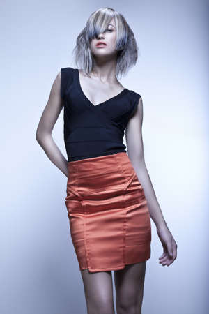 a bob: Modelo rubio con corte de pelo moderna y falda roja en estudio con fondo azul