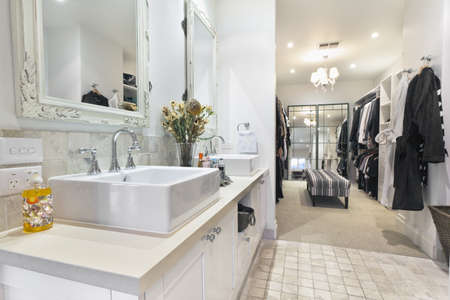 walk in closet: Stylish master bathroom with twin sinks and spacious walk in robe