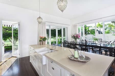 contadores: Cocina con estilo abierto con gran mesa de comedor con vistas a una piscina de golf y la nataci�n gruesa Foto de archivo