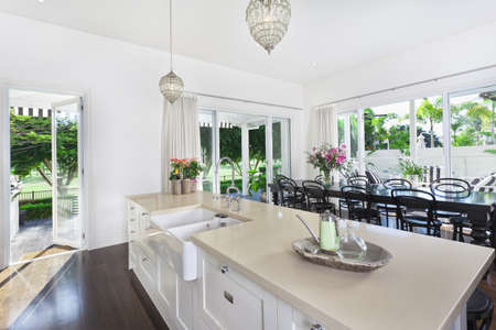 Stylish open kitchen with large dining table overlooking a golf coarse and swimming pool Stock Photo - 11800568