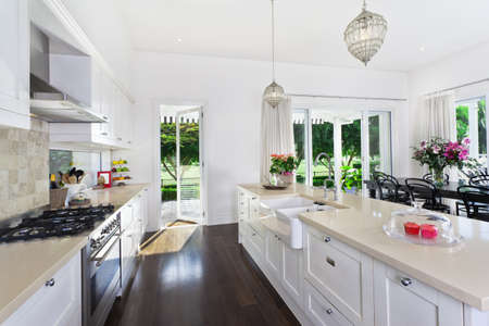 kitchen cabinets: Stylish open plan kitchen with stainless steel appliances and dining area overlooking a pool and golf course Stock Photo