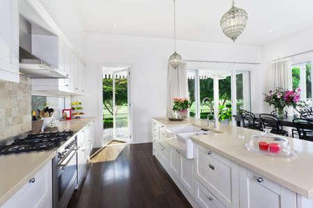 ceramiki: Stylowe otwarta kuchnia z nierdzewnej stali urządzeń i jadalnią z widokiem na basen i kurs golf