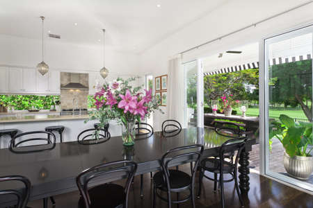 Stylish open plan kitchen with stainless steel appliances and dining area overlooking a pool and golf course photo
