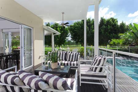 현관: 골프 코스와 수영장이 내려다 보이는 멋진 나무 야외 갑판 스톡 사진