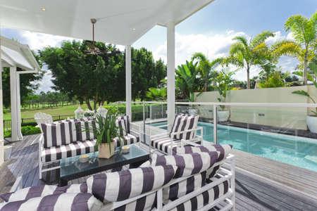 patio furniture: Elegante ponte di legno esterna che si affaccia un corso di piscina e campo da golf Archivio Fotografico