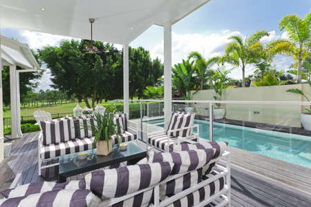 pool deck: Stylish wooden outdoor deck overlooking a swimming pool and golf course