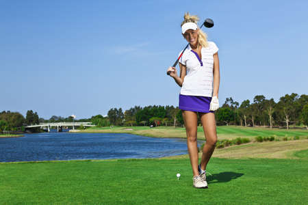 Attractive golfer girl on golf course with driver photo