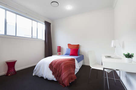 Modern bedroom with single bed, table and chair photo