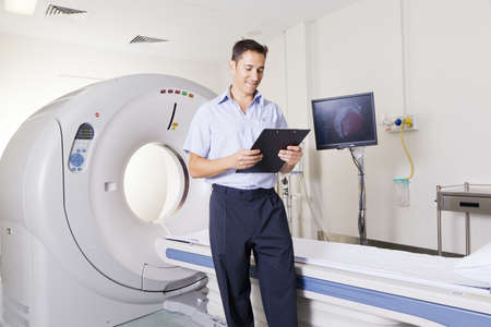 Young doctor standing in front of an MRI scanner photo