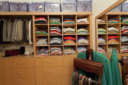 changing clothes: Mujer en pie de vestuario con camisas, pantalones, cinturones y cajones