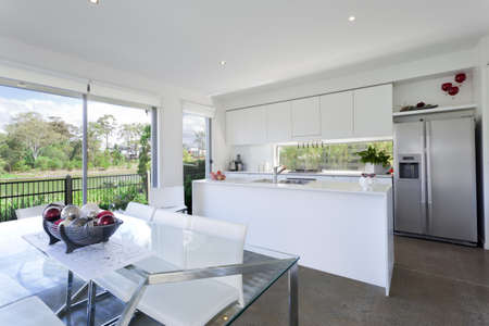 Modern kitchen and dining room with stainless steel appliances in Australian mansion