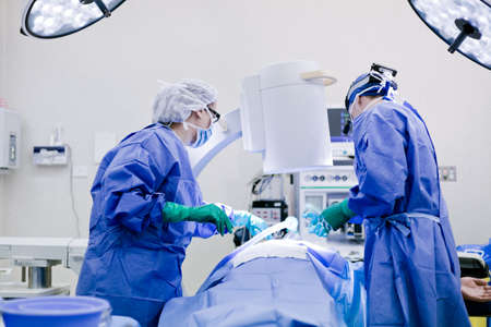 operating theater: Surgeon and nurse in operating theatre Stock Photo