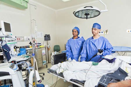 Surgery with operating table, nurses and surgeon photo