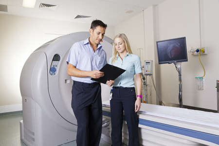 ct scan: Young doctor and nurse standing in front of an MRI scanner Stock Photo
