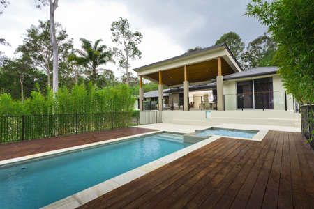 Modern backyard with swimming pool and outdoor entertaining area in Australian mansion