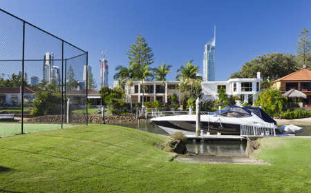 Waterfront backyard with tennis court and luxury yacht Stock Photo - 15616698