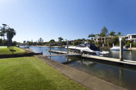 entertaining area: Waterfront backyard with tennis court and luxury yacht Stock Photo