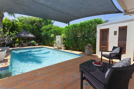 Modern backyard with swimming pool and Bali hutin Australian mansion