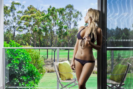 Attractive young woman on balcony overlooking a golf course Stock Photo - 17686858