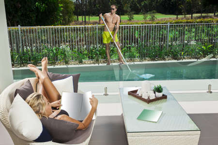 Attractive woman relaxing in backyard patio with pool boy cleaning the pool photo