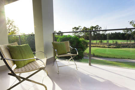 Chairs on modern balcony overlooking a gold course photo
