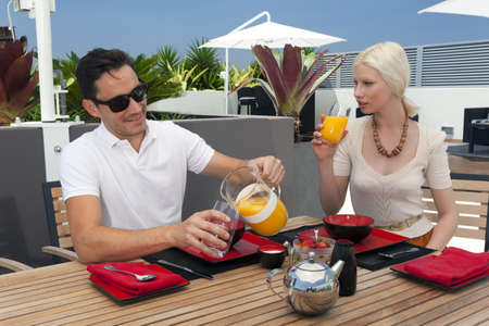 Young couple enjoying breakfast on modern balcony photo