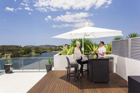 Young couple enjoying a drink on modern balcony Stock Photo - 18573635
