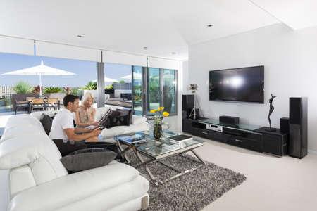 designers interior: Giovane coppia di relax sul divano in soggiorno di lusso