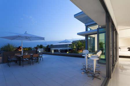 Balcon moderne au coucher du soleil dans le penthouse de luxe