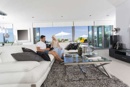 Young couple relaxing on couch in luxury living room photo