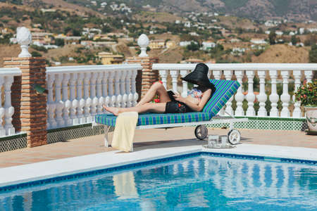 Young lady on sun lounger relaxing by the pool reading a book in a wide brimmed hat photo