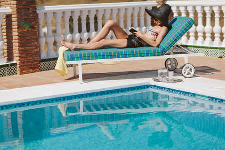 Attractive young girl laying in the sun poolside reading a book photo