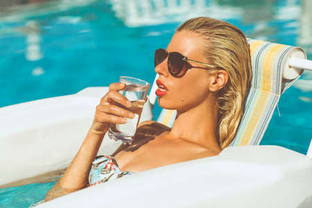 Young blonde model relaxing in pool drinking a glass of watter on a hot summers day Stock Photo - 23066988