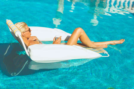 Young attractive blonde holding a glass of water and relaxing in pool on a hot summers day Stock Photo - 23066989