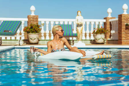 Young attractive blonde holding a glass of water and relaxing in pool on a hot summers day Stock Photo - 23067601
