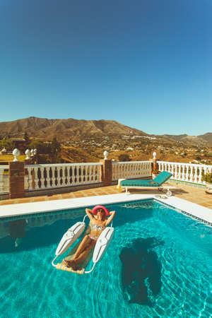 Young lady sunbathing in pool on a hot summers day in the spanish mountains photo