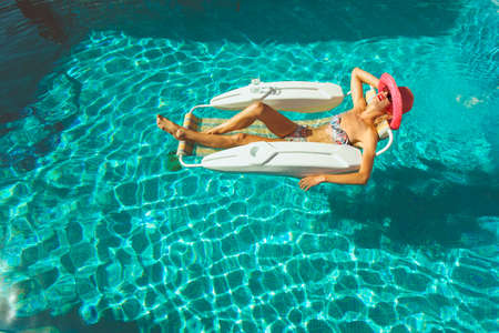 Young lady sunbathing in pool on a hot summers day Stock Photo - 23067010