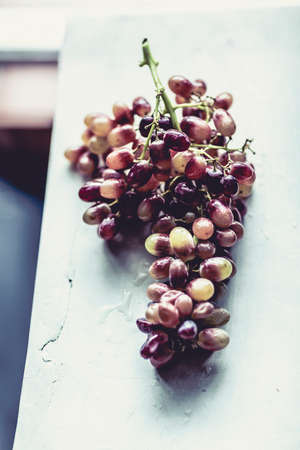 Bunch of juicy looking red grapes sitting on a rustic looking bench Stock Photo - 23018672