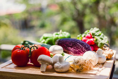 homegrown: Homegrown organic produce on wooden cutting board outdoors with greenery